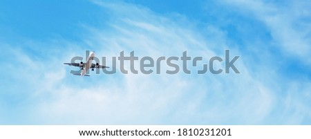 Beautiful Panoramic Background with flying plane in blue sky. Passenger airplane with landing gear released takes off in sky. Travel concept. Wide Angle Wallpaper or Web banner With Copy Space Photo stock ©