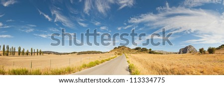 Beautiful panoramic photo of road through Sierra de Grazalema Natural Park. On the road. Blue cloudy sky. Golden fields with cypresses and rocks. Amazing scenery. Andalusia. Spain.