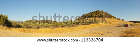 Beautiful panoramic photo of the amazing mountain landscape of Sierra de Grazalema Natural Park at sunset. Golden fields and olive trees. Blue sky. Andalusia. Spain.