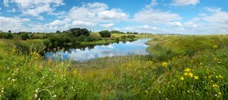 Beautiful panoramic rural landscape with calm river and green hills with blooming wild flowers and trees at sunny summer day.River Upa in Tula region,Russia.