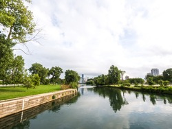 Beautiful panoramic skyline view over the Lincoln Park rowing canal or lagoon in Chicago with the city buildings in the distance and trees, grass and water reflecting the sky in the foreground.