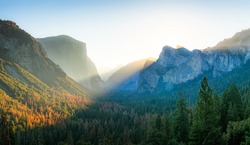 Beautiful panoramic sunrise at famous Tunnel View in scenic Yosemite Valley with El Capitan and Half Dome mountain summits in beautiful golden morning light, Yosemite National Park, California, USA