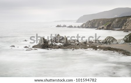 Beautiful panoramic view of a beach with rocks. Photo taken on the coast of Galicia, Spain during a cold and foggy day, long exposure
