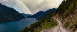 Beautiful Panoramic view of a Dirt Road in the Mountain Valley near a lake. Dramatic Summer with Rainbow Sky Artistic Render. Taken on Anderson Lake Rd, near Lillooet, BC, Canada.