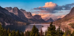Beautiful Panoramic View of a Glacier Lake with American Rocky Mountain Landscape in the background. Dramatic Colorful Sunrise Sky. Taken in Glacier National Park, Montana, United States.
