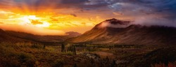 Beautiful Panoramic View of Colourful Fall Forest and Mountains in Tombstone. Sunset or Sunrise Sky Composite. Tombstone Territorial Park, Yukon, Canada. Nature Background Panorama