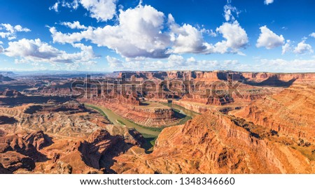Beautiful panoramic view of famous cliffs and canyons in Dead Horse Point State Park and Colorado River meanders on a sunny day with blue sky and scenic clouds in summer, American Southwest, Utah, USA