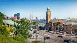 Beautiful panoramic view of famous Hamburger Landungsbruecken with historic commercial harbor and Elbe river on a sunny day with blue sky and clouds in summer, St. Pauli district, Hamburg, Germany