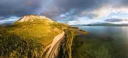 Beautiful Panoramic View of Golden Mountain and Forest beside Scenic Lake at Sunset in Canadian Nature. Aerial Drone Shot. Taken near Atlin, Yukon, Canada.