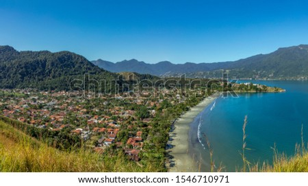 Beautiful panoramic view of Ilhabela island in background and coast of Sao Sebastiao, tropical island on the Brazilian sea coast during a sunny day of vacation and sightseeing.