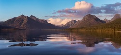 Beautiful Panoramic View of Lake McDonald with American Rocky Mountains in the background. Cololful Sunrise Sky Art Render. Taken in Glacier National Park, Montana, United States of America.