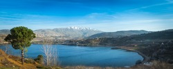 Beautiful panoramic view of Lake Ram (Birkat Ram) - a crater lake (maar) in the northeastern Golan Heights, with a Druze town of Majdal Shams and a snow-capped Mount Hermon in the background