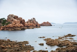 Beautiful panoramic view of Pink Granite Coast between Perros-Guirec and Ploumanach. Cliffs, boats and lighthouse on horizon. Cotes-d'Armor, Brittany, France
