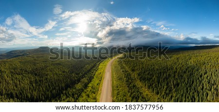 Beautiful Panoramic View of Scenic Road from Above surrounded by Lush Forest and Mountains. Aerial Drone Shot. Alaska Highway, West of Fort Nelson. Northern Rockies, British Columbia, Canada. Foto stock ©