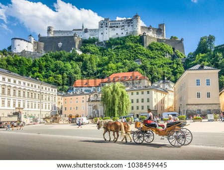 Beautiful panoramic view of the historic city of Salzburg with traditonal horse-drawn Fiaker carriage and famous Hohensalzburg Fortress on a hill on a sunny day with blue sky and clouds in summer #1038459445