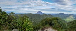 Beautiful panoramic view on dense tropical forest with smoking Gunung Sinabung volcano in the distance, near Berastagi, North Sumatra, Indonesia