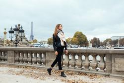 Beautiful Parisian girl walking near the Eiffel tower