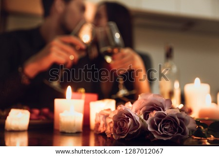 Photo of  Beautiful passionate couple having a romantic candlelight dinner at home, drinking wine, toasting
