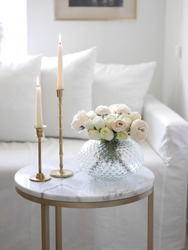 Beautiful pastel flower bouquet and tall candles on a marble coffee table in front of a white sofa.