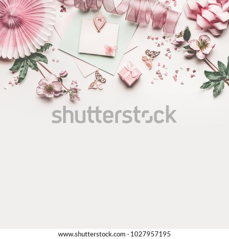 Beautiful pastel pink work space with flowers decoration,ribbon, hearts, bow and card mock up on white desk background, top view, flat lay, border. Wedding invitation or Mother Day greeting concept