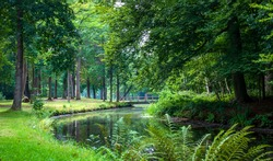 Beautiful pathway and big trees along small river in the green forest, european countryside landscape spring season. Pinetum Blijdenstein, park in Hilversum Netherland.Beautiful botanical garden.