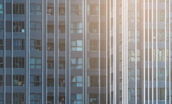 Beautiful pattern from many windows and balconies apartment building, crop part of condominium, Exterior building facade of modern apartments. Warm light on exterior building.