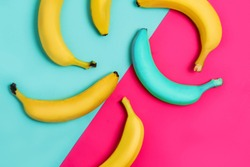 Beautiful pattern of yellow and one blue banana on paper colorful background. Flat lay
