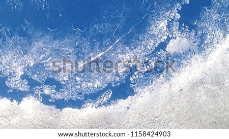 Stock Photo Beautiful patterns of melted snow on the window, similar to a planet visible from space, shore of the ocean