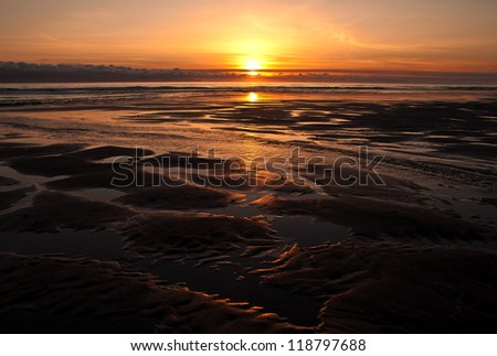 Beautiful patters formed by water flowing to the sea at sunset on an Alaskan beach.
