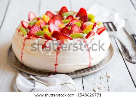 Beautiful Pavlova cake dessert with meringue and fresh fruit on white background Stock photo ©