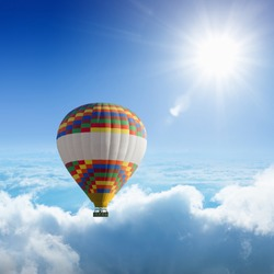 Beautiful peaceful background - hot air balloon flies very high in blue sky above white clouds, bright sun shines