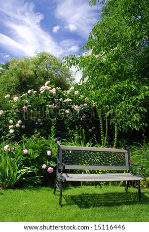 Beautiful peaceful garden with a bench surrounded by pink roses