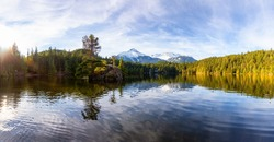Beautiful Peaceful Panoramic View of Levette Lake with famous Tantalus Mountain Range in the background. Taken in Squamish, North of Vancouver, British Columbia, Canada. Nature Panorama