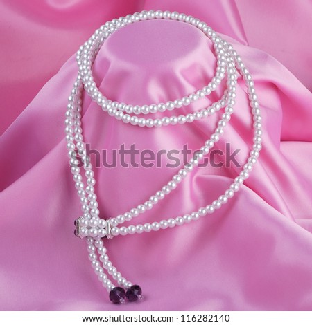 beautiful pearl necklace on pink silk background
