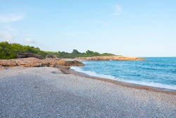 Beautiful pebble or stone beach. Paradise atmosphere with no tourists. Mesmerizing coastline. Perfect desktop background. Alcossebre, Costa del Azahar, Spain