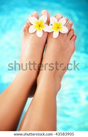 Beautiful pedicured female feet and tropical flowers.