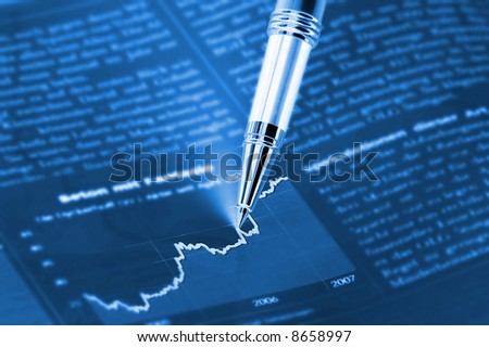 Beautiful Pen pointing on a diagram on an finance newspaper
