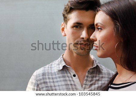Beautiful pensive man and woman stand near gray wall; focus on woman