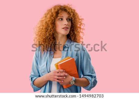 beautiful pensive student holding books isolated on pink