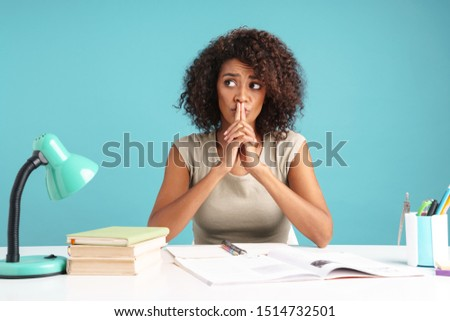 Beautiful pensive young african businesswoman casually dressed sitting at the desk isolated over blue background, studying