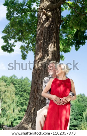 Beautiful people. Beautiful senior woman looking amazing in her red dress while standing near the tree with her loving husband