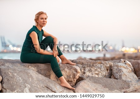 Beautiful people Fitness woman with short blonde hair sitting after workout in a sea beach side . Sport and Healthy Lifestyle Concept