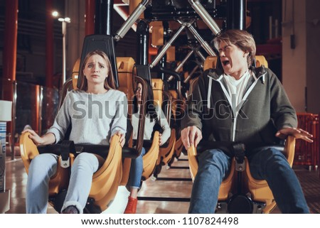 Beautiful people ride on attractions. Funny moments of friends in lunar park.