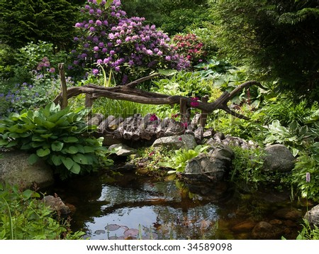 Beautiful perfect backyard landscaped garden with wooden bridge