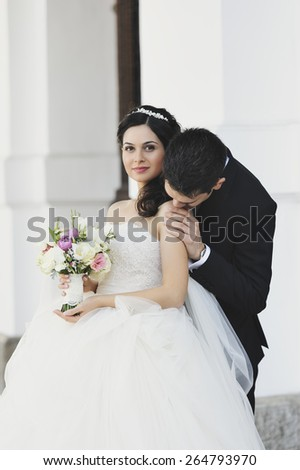 Beautiful, perfect couple posing on their wedding day. The groom is kissing his bride on the shoulder