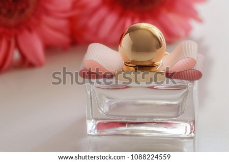 Beautiful perfume bottle with pink flower on the back.  Luxury perfumery background.Floral fragrance concept. #1088224559
