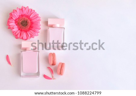 Beautiful perfume bottle with pink flowers and macaroons.  Luxury perfumery background with copy space. Sweet and Floral fragrance concept. #1088224799