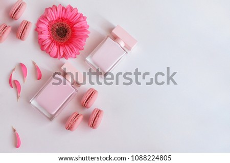 Beautiful perfume bottle with pink flowers and macaroons.  Luxury perfumery background with copy space. Sweet and Floral fragrance concept. #1088224805