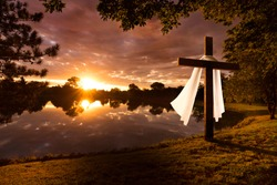 Beautiful photo illustration of an Easter morning sunrise with a cross and burial fabric by a calm lake. The warm light almost announces Jesus's rising from the dead.