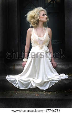 Beautiful photo of a tall woman in a white dress with a dark background